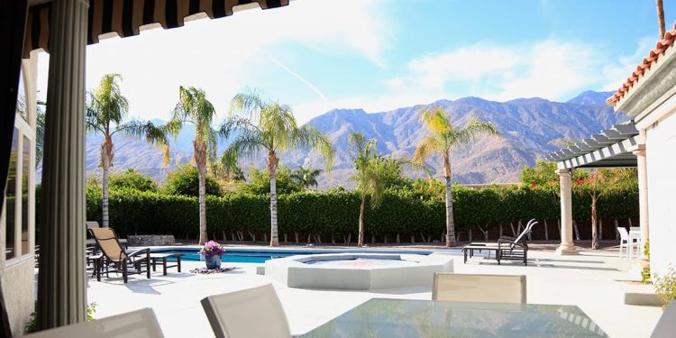 A patio in Palm Springs with a pool, hot tub and palm trees. A hedge lines the back of the pool area and mountains are visible over top.