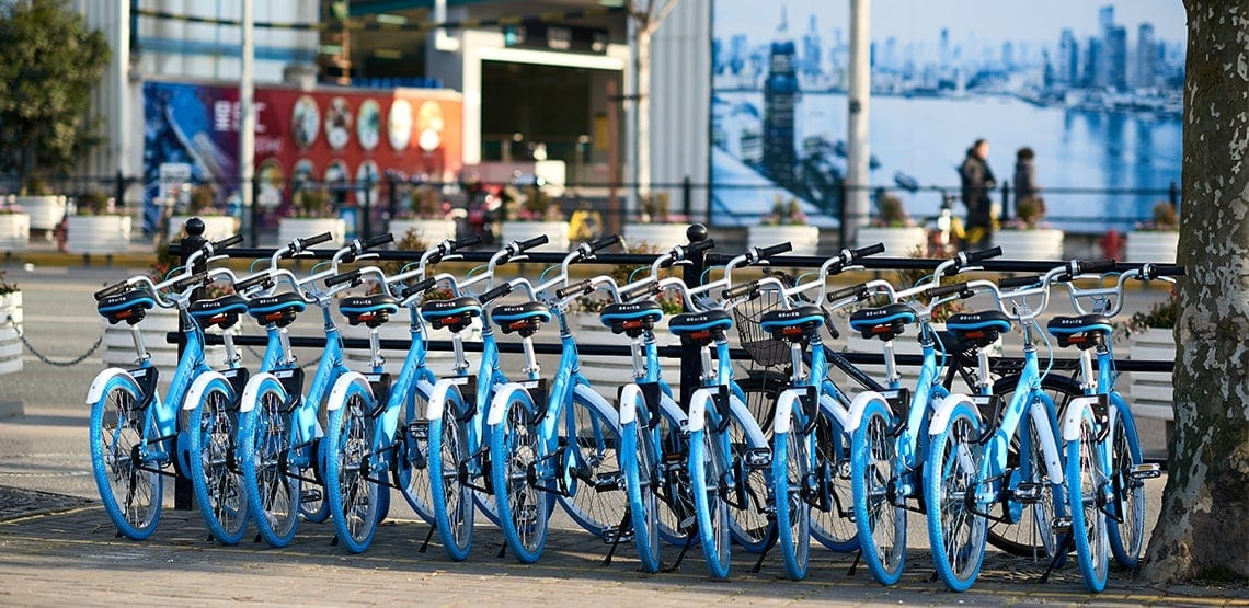 Row of blue rental bikes are lined up at the side of a road.