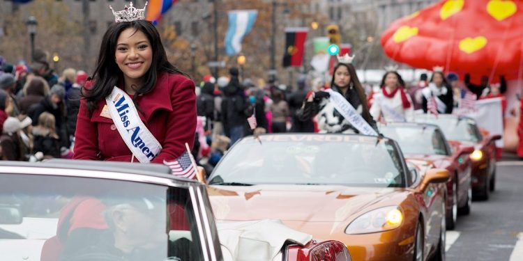 Miss America Outstanding Teen 2015, Olivia McMillan, waves to the crowds at Love Park as she sits in the back of a convertible that takes part in the annual Thanksgiving Day Parade in Philadelphia.