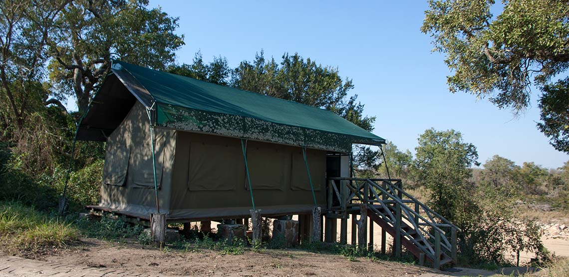 Small brown hut with green tarp roof on a wooden platform with wooden stairs leading up to it.