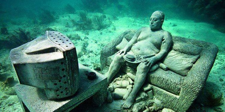 Statue of a man sitting on a couch watching TV, all immersed on the ocean floor.
