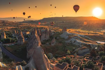 Hot air balloons over Cappadocia, rock formations rising into the sky.