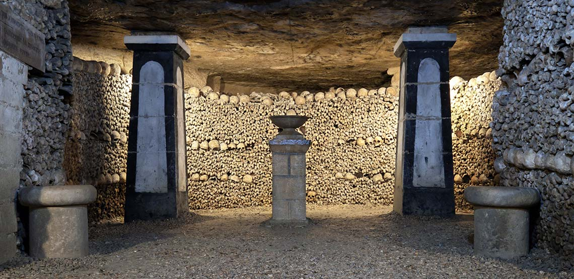 underground walls lined with human bones in the Paris catacombs