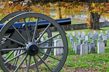 A canon sitting in front of rows of white graves.