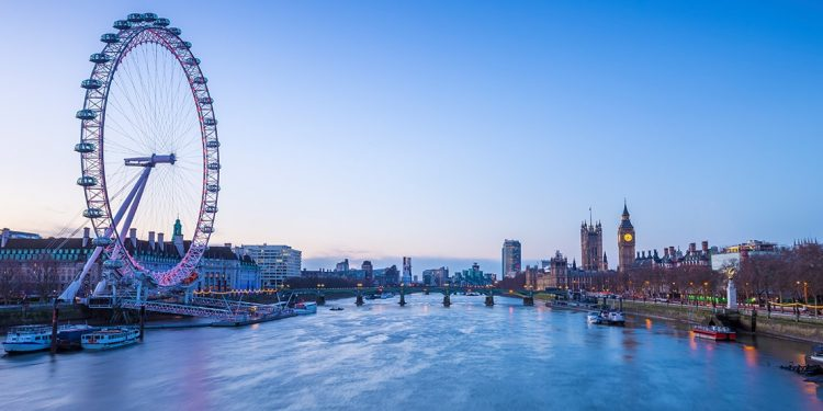 A river with giant Ferris wheel on one side, with bridge crossing over, and Big Ben visible in the distance.
