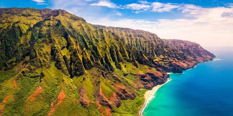 Green mountains along a blue coastline.