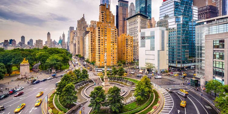 Roundabout with skyscrapers on right side and Central Park on the left. There is a ring of trees in the middle of the roundabout with a statue in the middle.