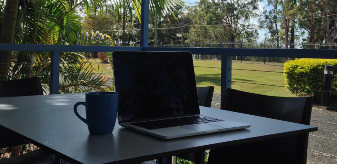 Macbook sitting on square table with blue mug beside it. Tropical nature in the background.