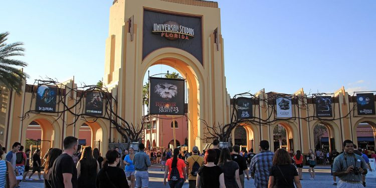 Entrance to Universal Studios with people milling about and vines on entryway.