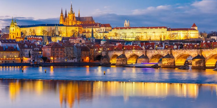 Prague castle well lit against night sky