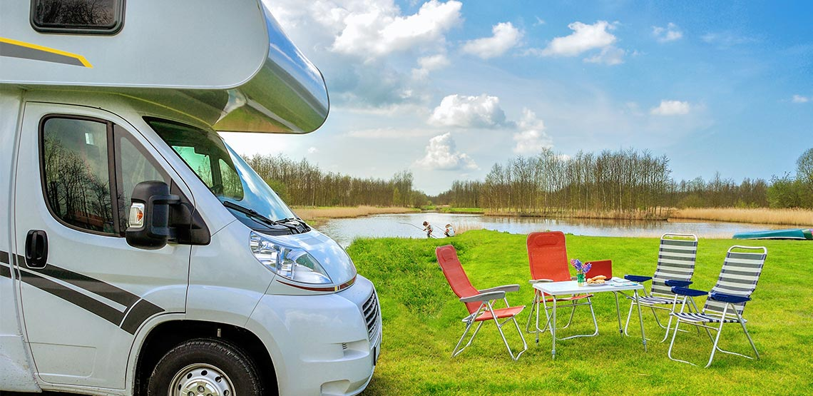 RV parked beside a folding table and lawn chairs. Two children are fishing at a small lake in the background.
