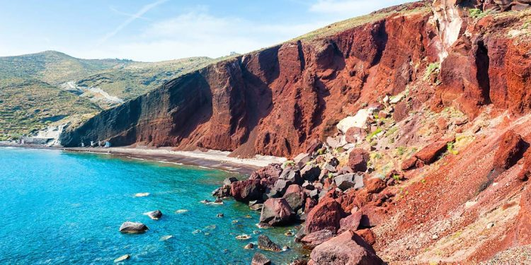 Red cliff stretching along coast of blue ocean with a strip of beach at the bottom.