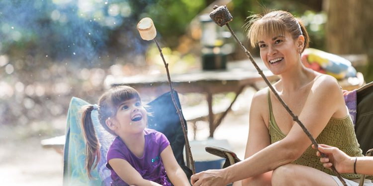 Little girl and mother sitting in lawn chairs holding sticks with roasted marshmallows on the ends.
