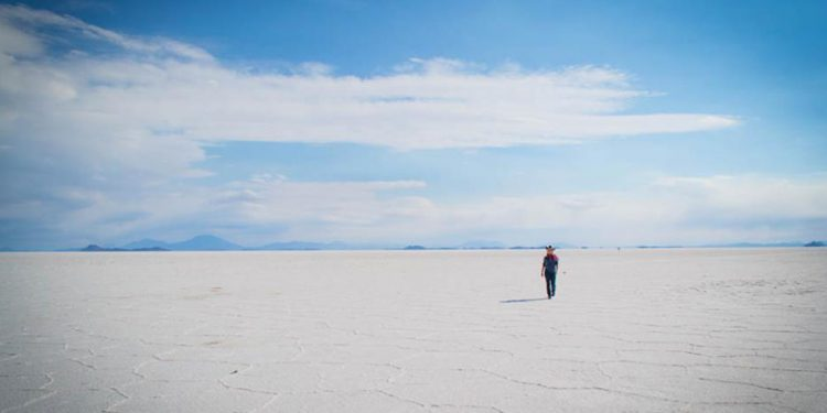 A figure standing on a white expanse of ground with blue skies above.