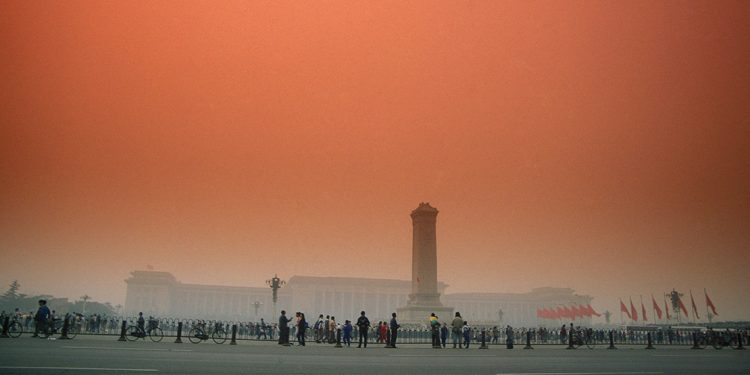 Foggy morning with orange sky. Tower monument in front of stately building. People milling about out front.