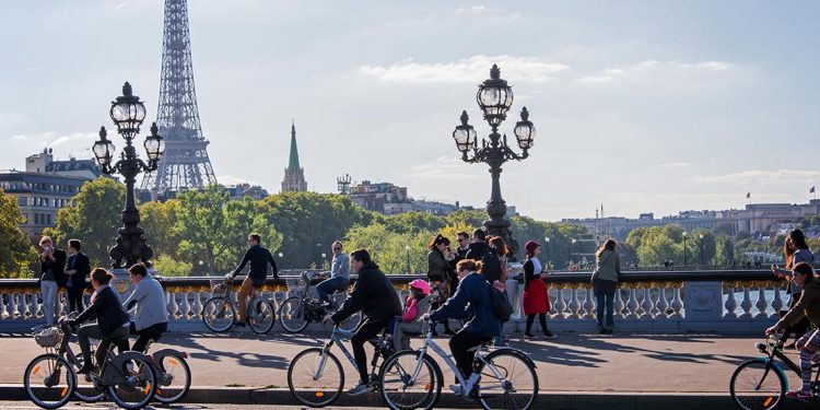 Cyclists riding along bridge with Eiffel Tower in background