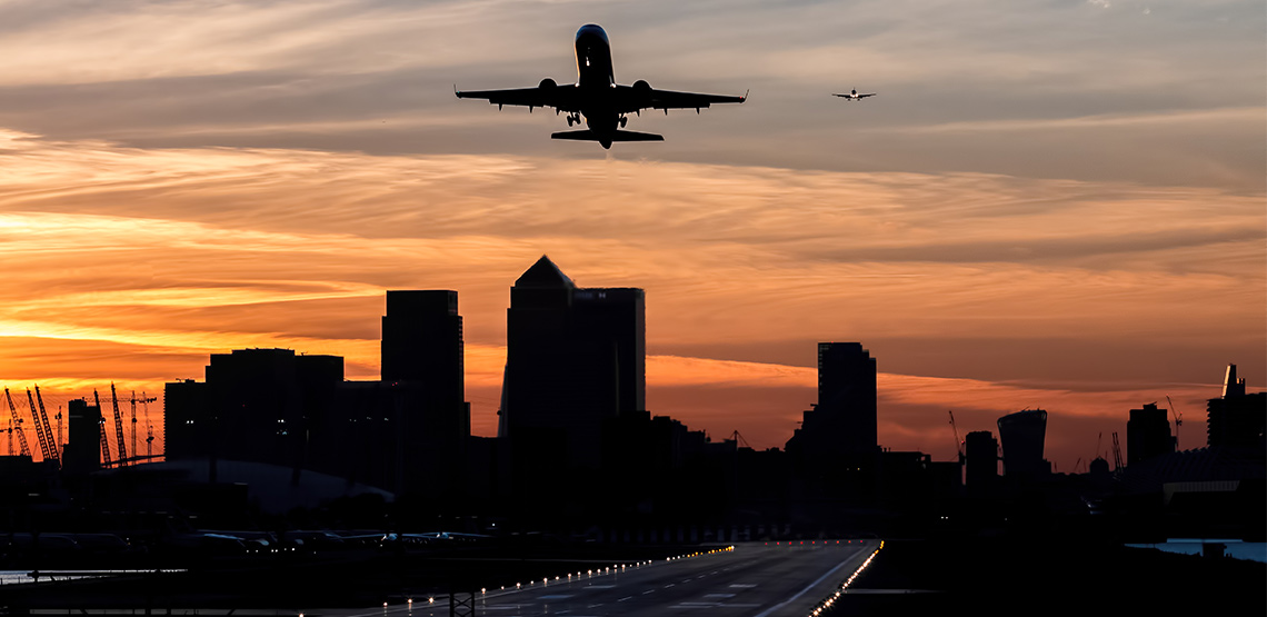 Plane taking off of runway with buildings silhouetted in background.