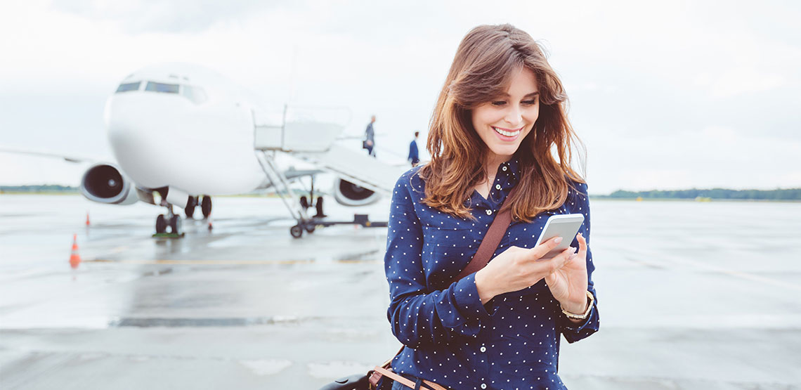 A woman stands off to the side of an airplane, looking at her phone.