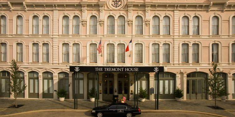 Three storied hotel front with towncar parked out front.