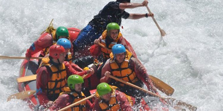 Seven rafters and a guide in a red raft with white water all around.