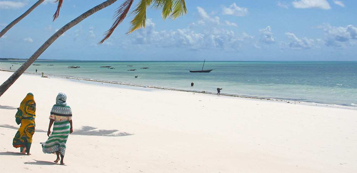 Women in traditional Zanzibar dress walk down the beach in Nungwi.