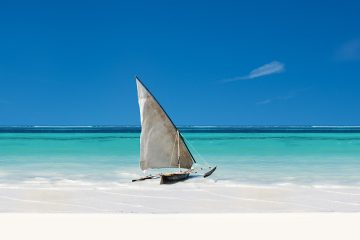 A traditional dhow boat sits in the turquoise water off Zanzibar.