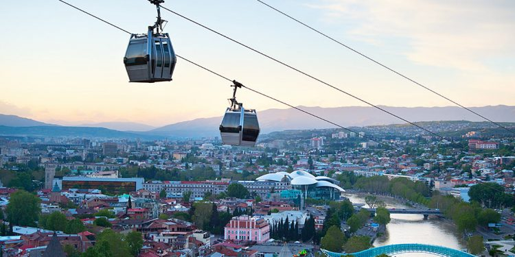 Two cable cars with city and river down below.
