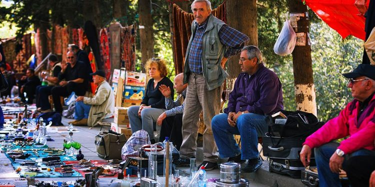 People sitting with wares out on ground in front of them and rugs hung behind.