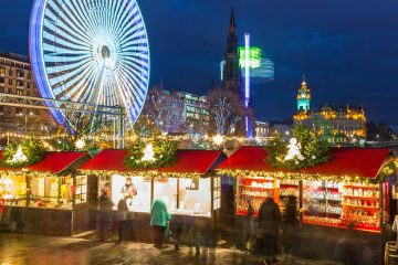 Christmas stalls set up outside with Ferris wheel and tower in background.