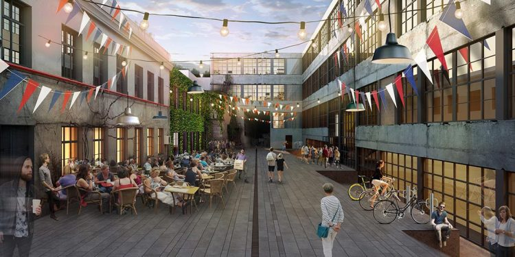 Courtyard with warehouses on either side. People sitting at patio sets.