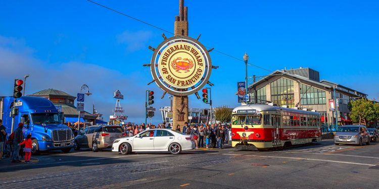 "Corner of street with streetcar and giant sign reading ""Fisherman's Wharf of San Francisco."""