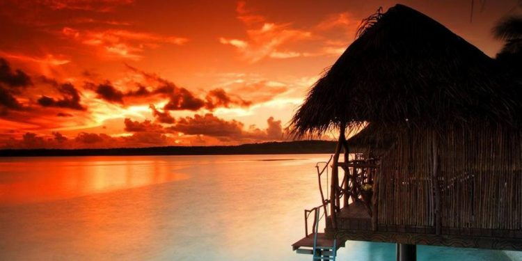 Hut over top water at sunset.