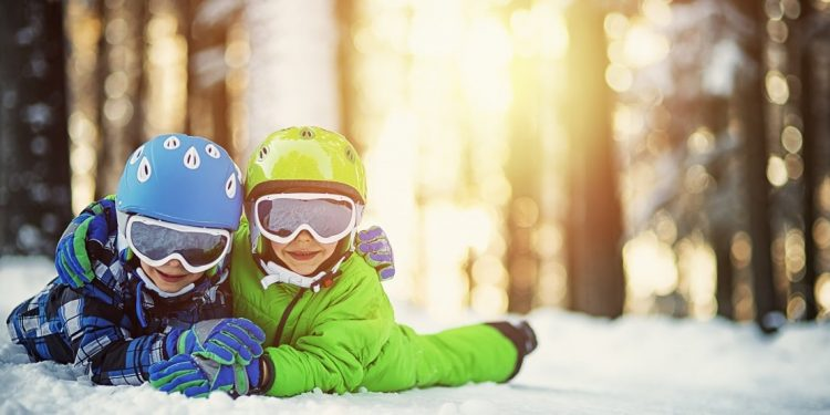Portrait of little brothers in ski outfits lying on snow and smiling into the camera. Kids are wearing colorful helmets and ski goggles.