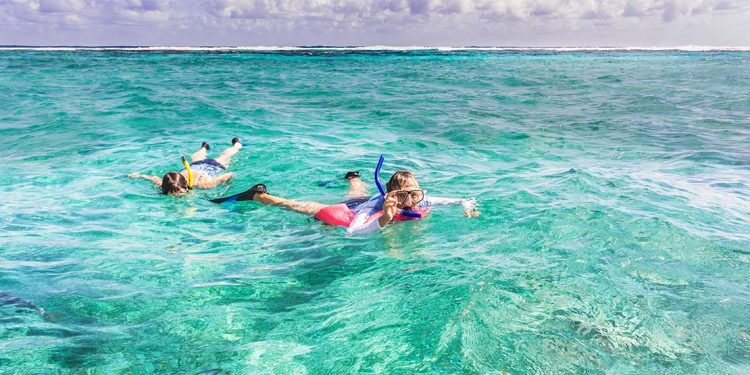 Two kids snorkeling in ocean.
