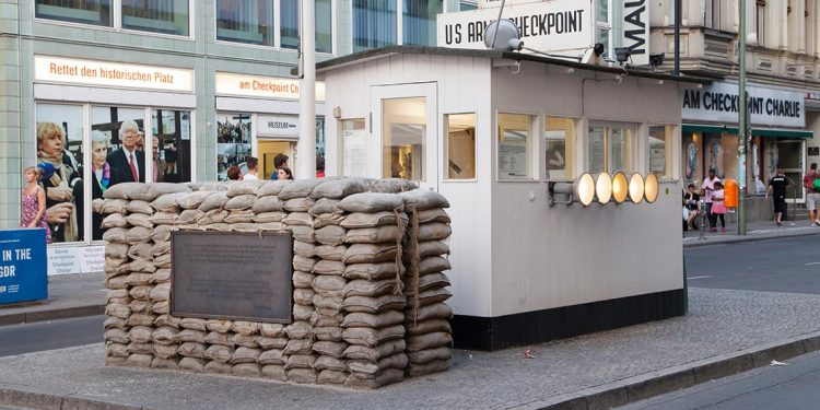 Small checkpoint building with sandbags in middle of street.