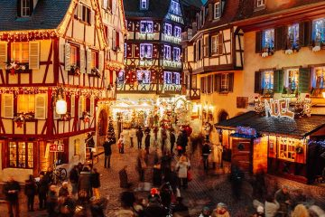 Busy cobblestone street with old country style buildings decorated with Christmas lights.
