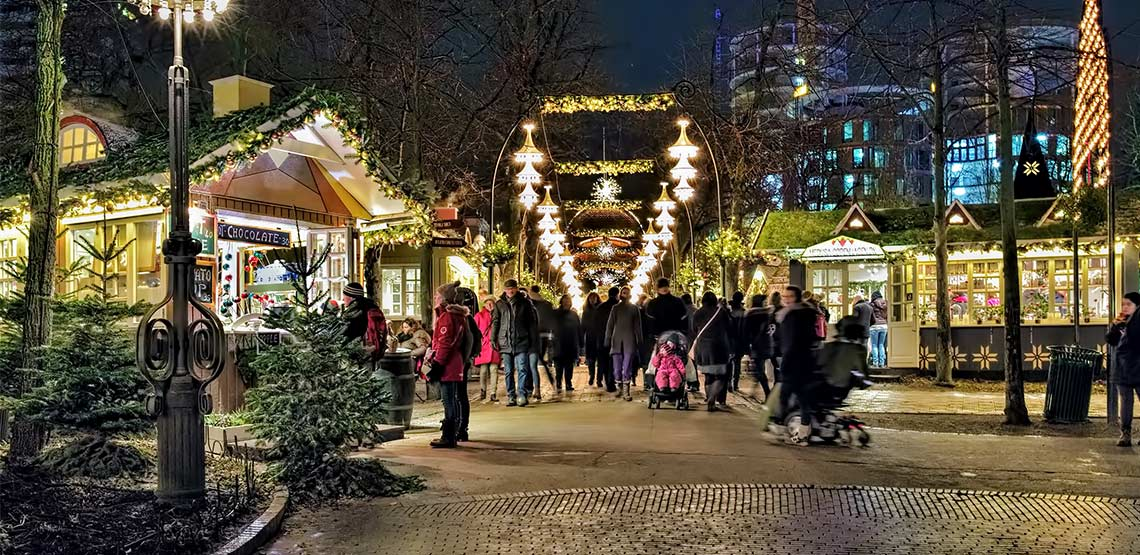 Christmas market with lights above pathway and small boots on either side.