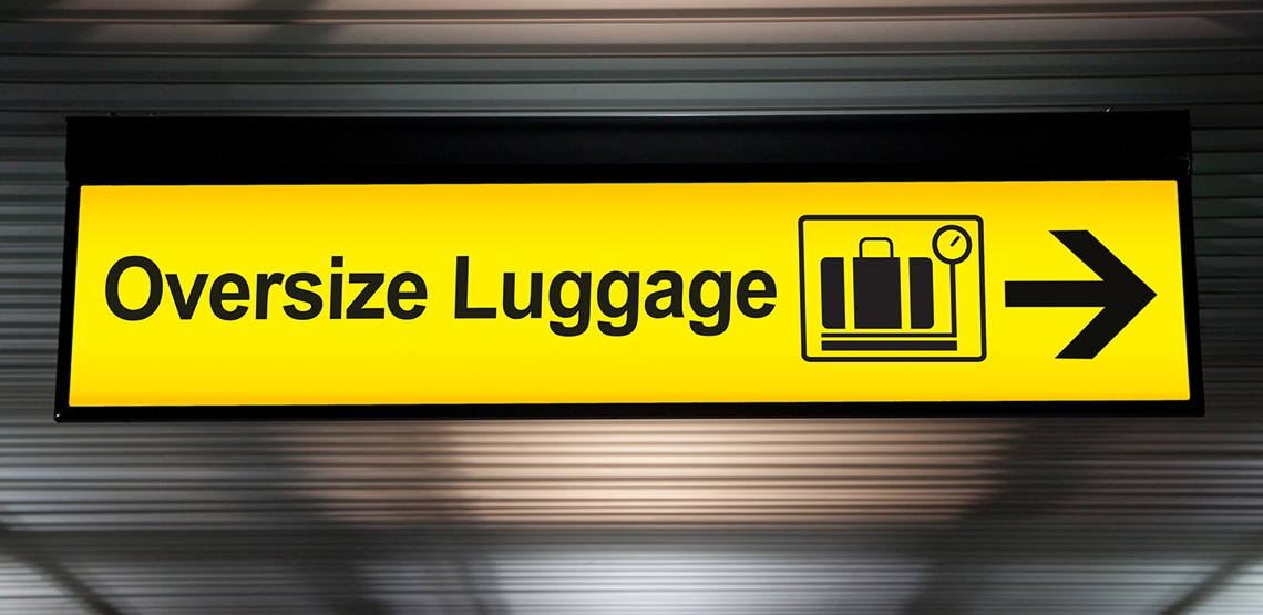 "Sign at airport with arrow reading ""Oversize Luggage"""