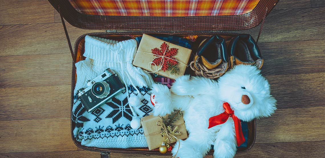 Two wrapped gifts in suitcase with camera, sweater, boots and teddy bear.