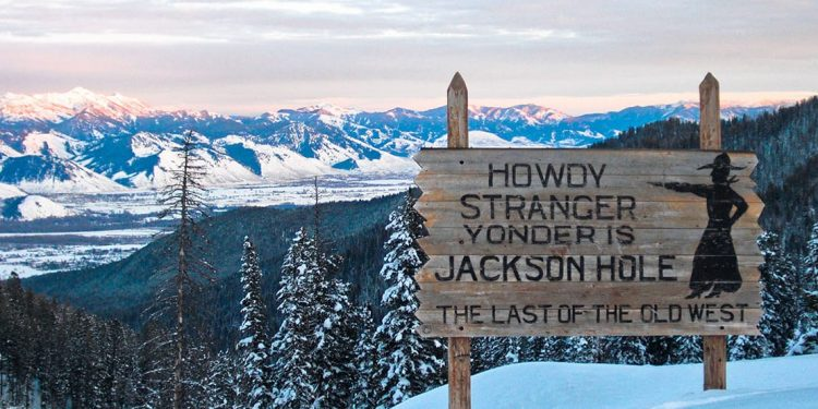"Sign reading ""Howdy stranger, yonder is Jackson Hole, the last of the old west"" on top of the mountain."