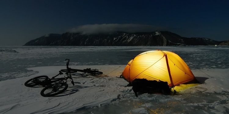 An orange tent and bikes lies on the surface of frozen lake at night.