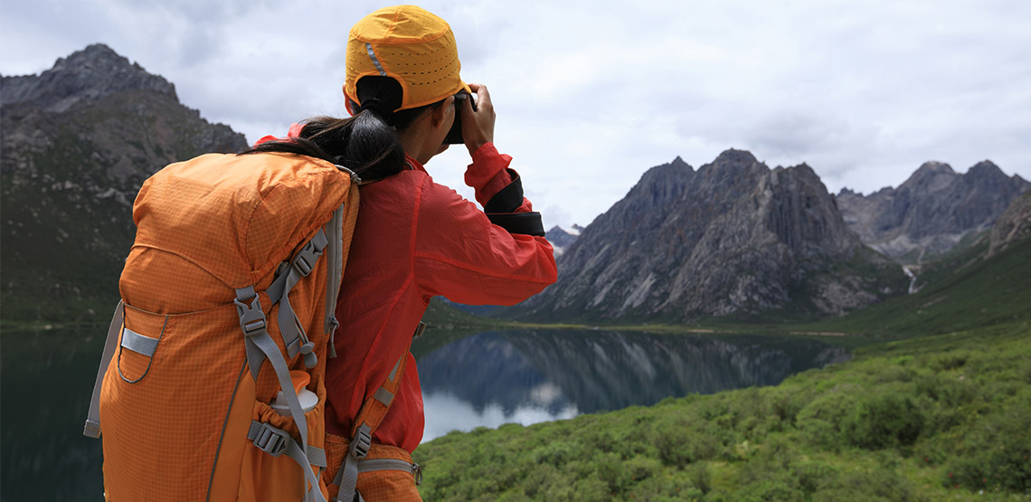 Backpacker taking photo of a lake and mountains