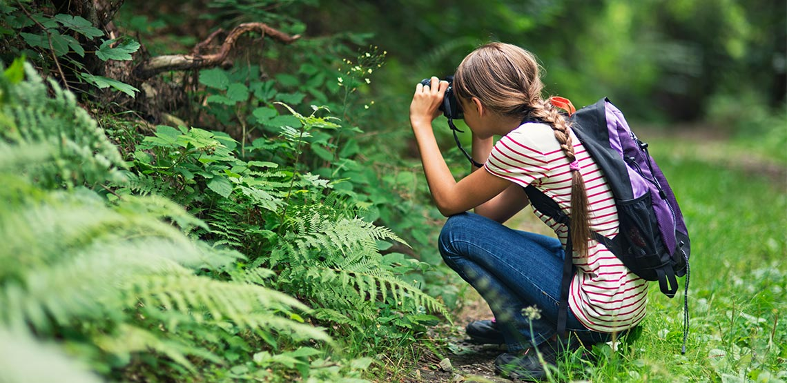 Young girl crouching to take photo of a plant