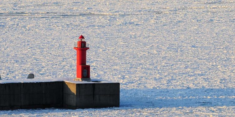 Red lighthouse and floating ice in The Sea of Okhotsk