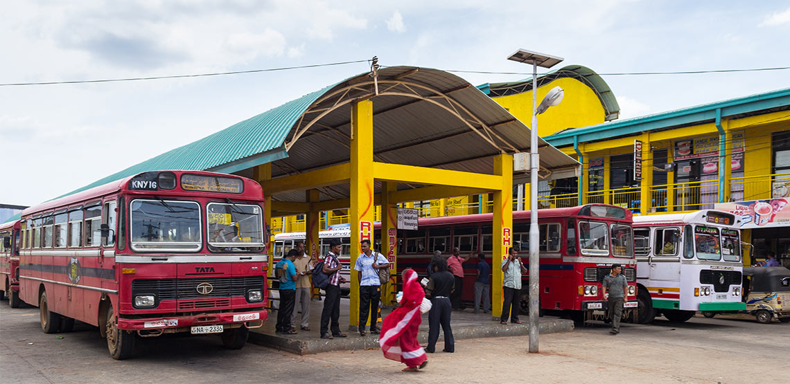 Bus station in India with red buses and people loitering.