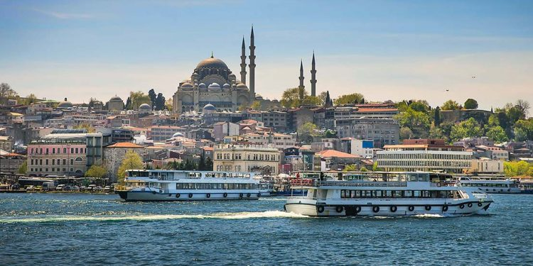 A view of Istanbul from the water, ferries pulling up to a port as minarets rise toward the sky