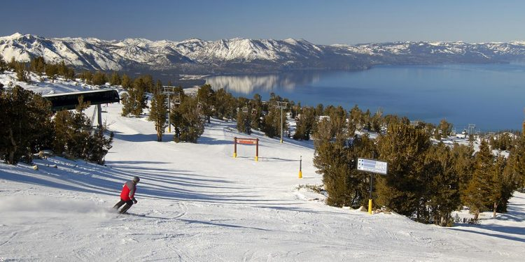 Skier on a run with lake and mountain range in background.
