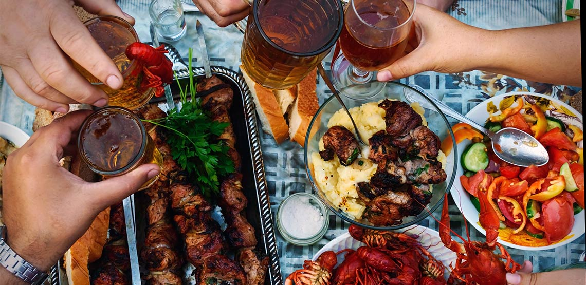Table with food and people holding drinks.