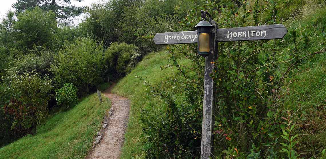 """Path and signpost reading """"green dragon"""" and """"hobbiton"""""""
