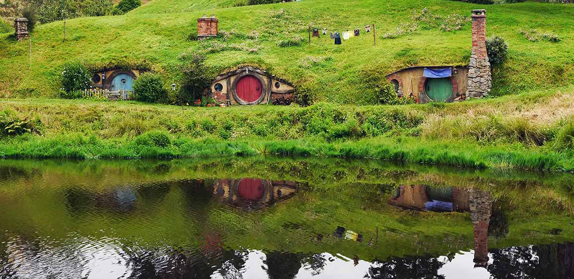 Three hobbit holes set in hillside with pond in front